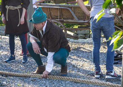 Uczestnik zabawy przebrany za Robin Hooda mierzy linę