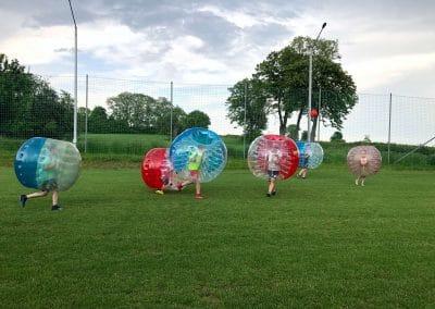 Chłopcy z klubu sportowego w krakowie grają w Bubble Football - piłkę nożną w kulach
