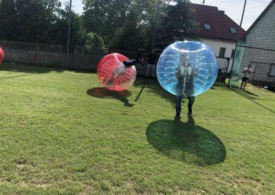 Gramy w Bubble Football w Łodzi na trawiastym boisku. Jeden z uczestników wykonuje salto